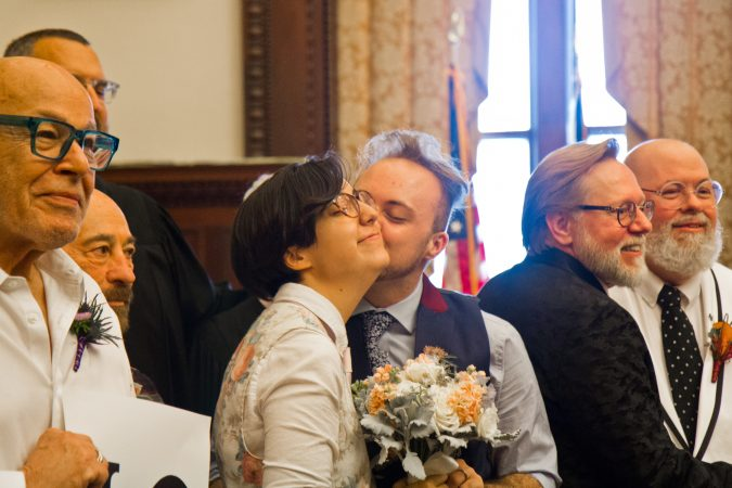 Maggie Alvarez receives a kiss from their spouse Emmett Bikowski after they were married at City Hall Thursday. (Kimberly Paynter/WHYY)