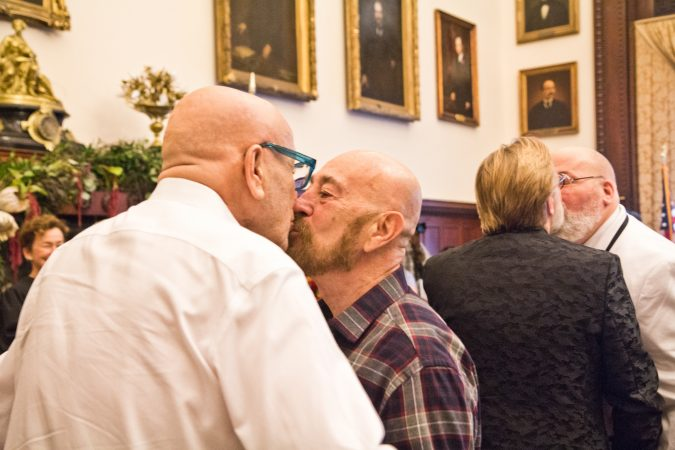 Charles Massucci kisses his partner of 47 years, Joseph DiDio, as they renew their vows at the National Coming Out Day event at City Hall Thursday. (Kimberly Paynter/WHYY)