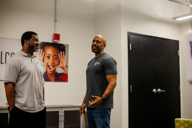 Sharif El-Mekki (left), principal at Mastery Charter's Shoemaker campus and Miles WIlson, CEO and President of Education Works chat in the office of Wilson's organization. (Brad Larrison for WHYY)