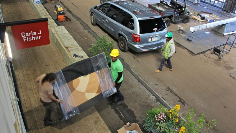 Workers move artwork into the Carla J Fisher studio on the Cherry Street Pier. (Emma Lee/WHYY)