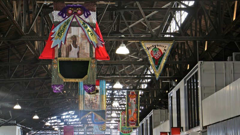Banners celebrating Philadelphia's neighborhoods hang from the rafters at the Cherry Street Pier. (Emma Lee/WHYY)