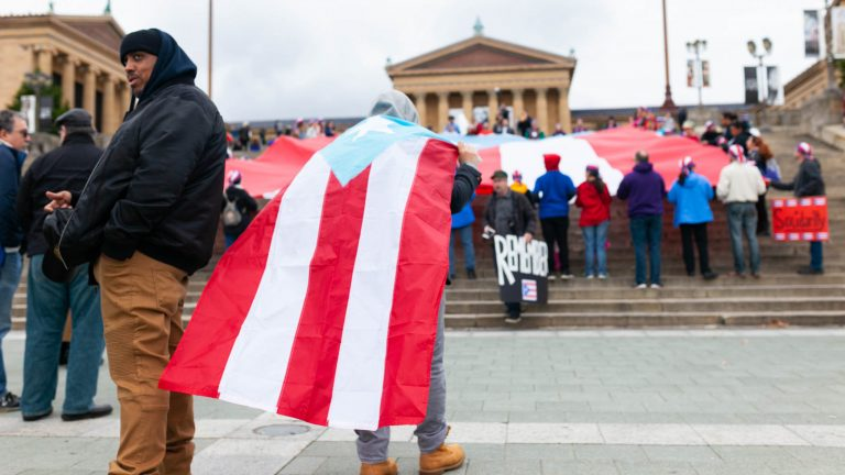 A man wears a cape made from a Puerto Rican during an event to remember the people who died in Hurricane Maria in Puerto Rico. The group of activists gathered on the steps of the Philadelphia Museum of Art on Oct. 13, 2018. (Miguel Martinez for WHYY)