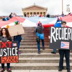 Yecenia Vazquez (left) and Jaime Knowles hold signs in front of a large Puerto Rican flag that was laid it at the steps of the Philadelphia Museum of Art. A group of activist smarched the Benjamin Franklin Parkway to commemorate the people who died in Hurricane Maria in Puerto Rico. (Miguel Martinez for WHYY)
