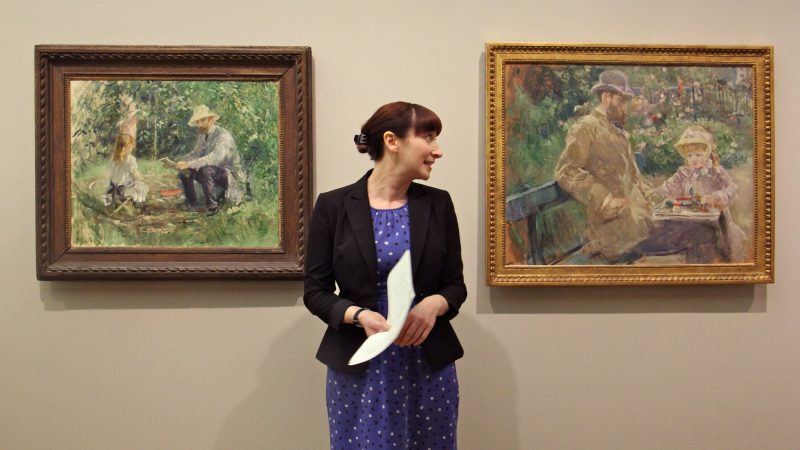 Curator Nicole Myers of the Dallas Museum of Art stands between two Berthe Morisot paintings depicting the artist's husband, Eugène Manet, and daughter, Julie. Eugène Manet is the only man depicted in the Barnes Foundation exhibit of Morisot's work. (Emma Lee/WHYY)