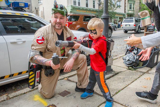 Dan Ritchie of Philadelphia Ghostbusters shows 3-year-old Jack Dorkus the tools of his trade.  Philadelphia Ghostbusters is licensed by Sony Entertainment. (Jonathan Wilson for WHYY)