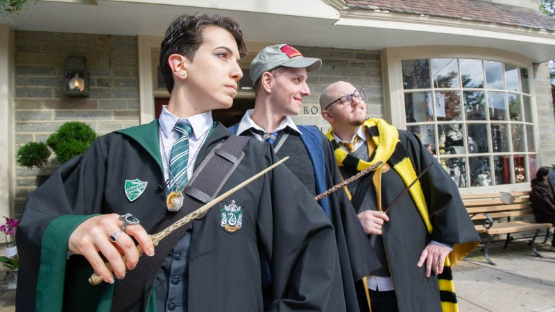 From left, representing the Hogwarts Houses of Slytherin, Ravencroft, and Hufflepuff are Grace Candido-Beecher, Irvin Khaytman, and Nick Beecher. (Jonathan Wilson for WHYY)