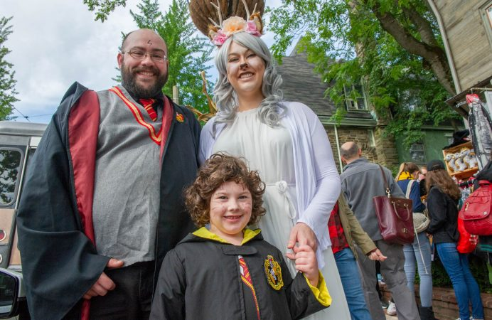 In Harry Potter regalia, John Bangor, Ellie Bangor, 6, and Lee Bangor from Doylestown, take in the sites on Germantown Avenue. (Jonathan Wilson for WHYY)
