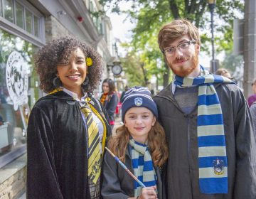 Wizards for a day (from left) Charlene Delos Santos, Harley Birkmire, and Joe Birkmire, show off their attire on Germantown Avenue at the Chestnut Hill Witches and Wizards Festival. (Jonathan Wilson for WHYY)