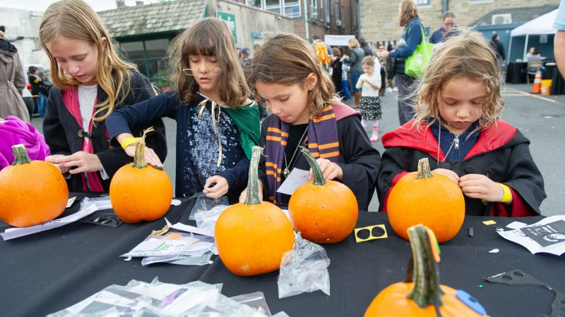 From left, Lyla Storm, Ruby Hayes, Maddie Jones, and Bianca Jones peel off stickers to make faces on pumpkins. (Jonathan Wilson for WHYY)