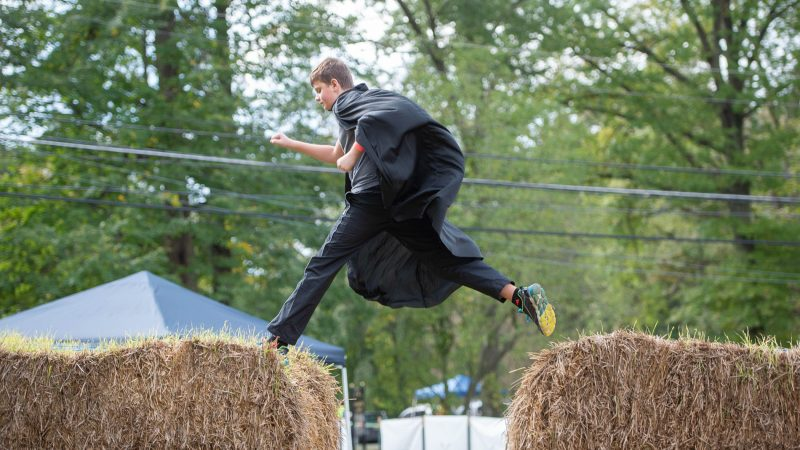 Nicholas McNamara leaps across bales of straw, part of a straw maze created on the lawn of the Woodmere Art Museum for the Witches and Wizards Festival. (Jonathan Wilson for WHYY)
