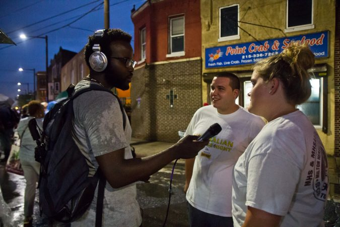 Reporter Darryl Murphy talks to Point Breeze residents Kelly Murray and Anthony Coskuy at the Point Breeze Night Market. (Kimberly Paynter/WHYY)