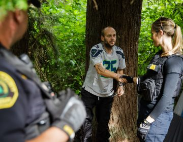 Social worker, Lauren Rainbow (right), along with Police Officer Mike Buell (left) meet a man illegally camped in the woods in Snohomish County. They are part of a new program in the county that helps people with addiction, instead of arresting them. (Leah Nash for Finding Fixes Podcast)