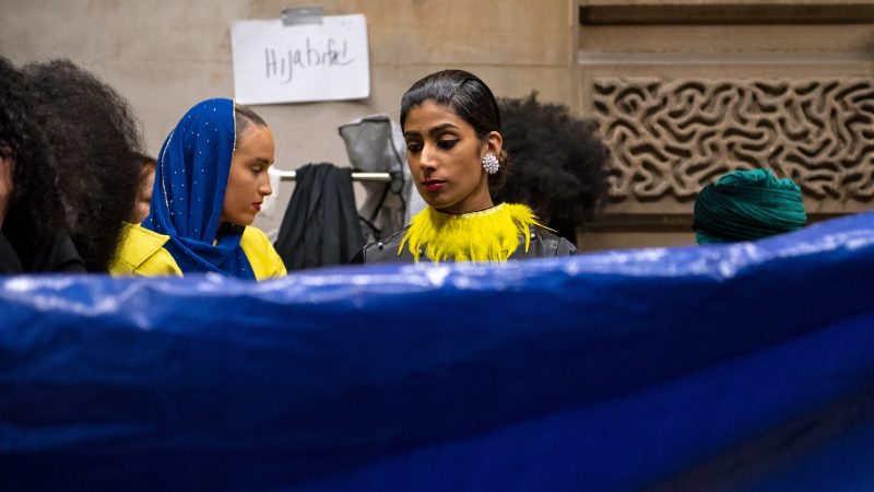 Models wait backstage as a tarp is laid out to prevent tearing at Philadelphia Fashion Week, held at Dilworth Park. (Kriston Jae Bethel for WHYY)