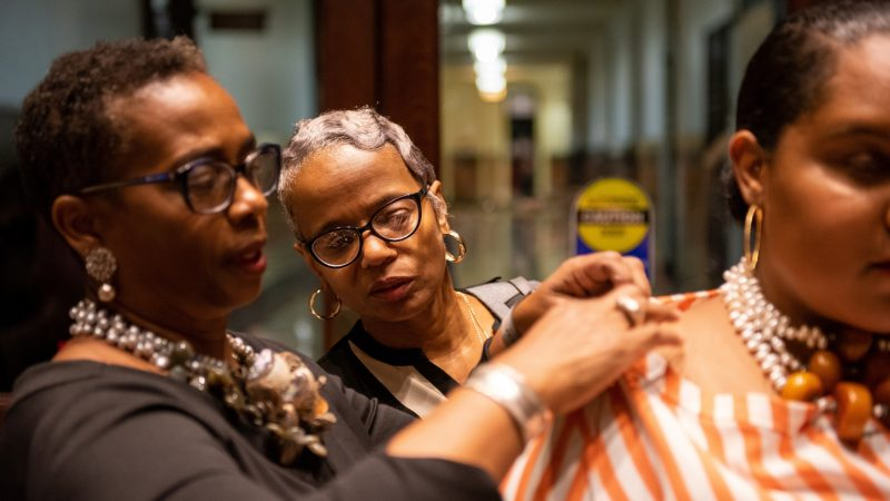 Donna Thomas looks on as her sister-in-law, designer Julia Turner Lowe of JTL Designs, makes adjustments before the Friday night runway show at Philadelphia Fashion Week, held at Dilworth Park. (Kriston Jae Bethel for WHYY)