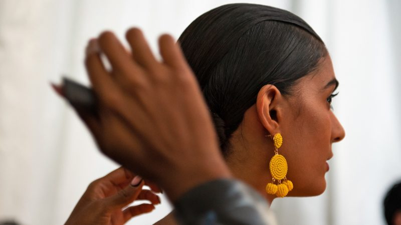 A stylist makes final touch-ups to a model's hair moments before she steps onto the runway at Philadelphia Fashion Week, held at Dilworth Park. (Kriston Jae Bethel for WHYY)