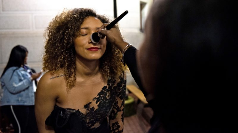 Maylynn Tamarez has her makeup retouched backstage at Philadelphia Fashion Week, held at Dilworth Park. (Kriston Jae Bethel for WHYY)