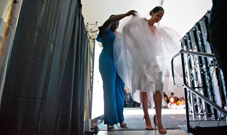 Designer Symone Gaither helps a model off the runway at the conclusion of Friday's show at Philadelphia Fashion Week, held at Dilworth Park. (Kriston Jae Bethel for WHYY)