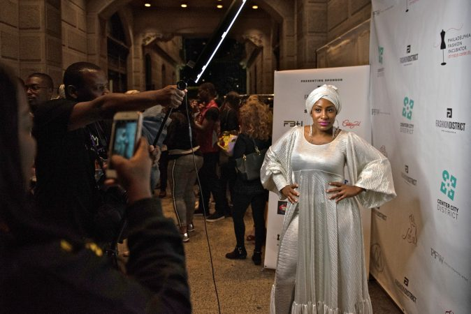 A Philadelphia Fashion Week attendee posses for her own photoshoot following Friday night's runway show, held at Dilworth Park. (Kriston Jae Bethel for WHYY)