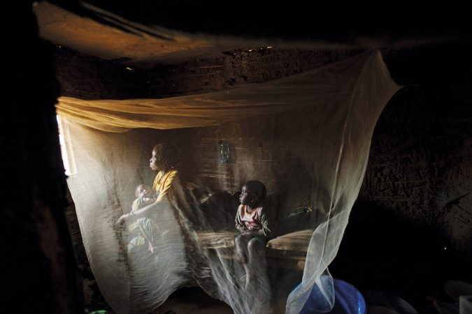 Kahindo, twenty, sits in her home with her two children born out of rape in North