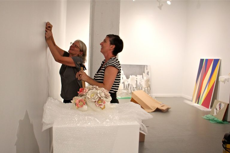 Jane Irish (left) and Mary Henderson of Tiger Strikes Asteroid galleries hang their first show at the Crane Arts Building. (Emma Lee/WHYY, file)