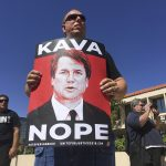 A man holds up a sign during a protest against Supreme Court nominee Brett Kavanaugh outside the offices of Arizona Sen. Jeff Flake in Phoenix, Friday, Sept. 28, 2018. (AP Photo/Patricio Espinoza)