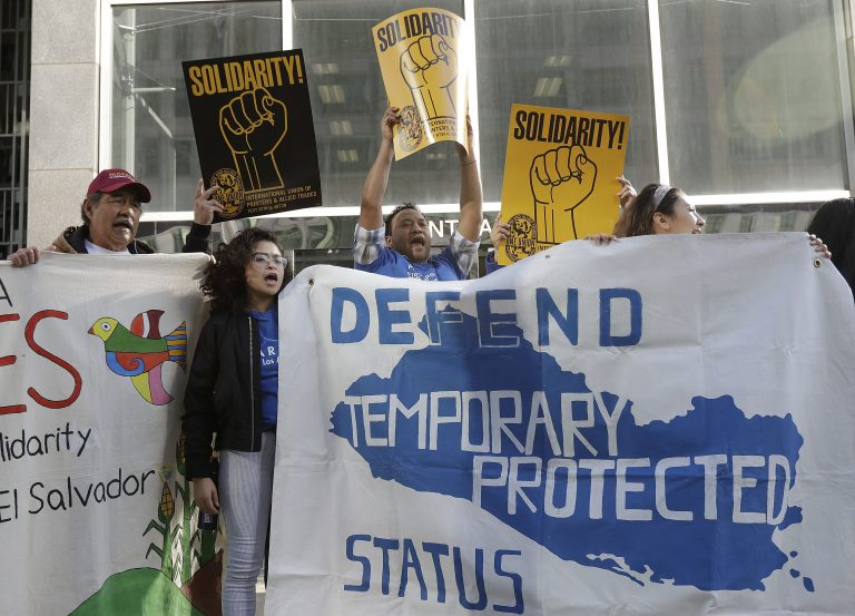 In this Monday, March 12, 2018, file photo, supporters of temporary protected status immigrants hold signs and cheer at a rally outside of a federal courthouse in San Francisco. A judge on Wednesday, Oct. 3, 2018, blocked the Trump administration from ending protections. (Jeff Chiu/AP Photo, File)