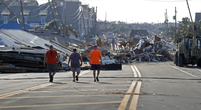 People walk amidst destruction on the main street of Mexico Beach, Fla., in the aftermath of Hurricane Michael on Thursday, Oct. 11, 2018. (AP Photo/Gerald Herbert)