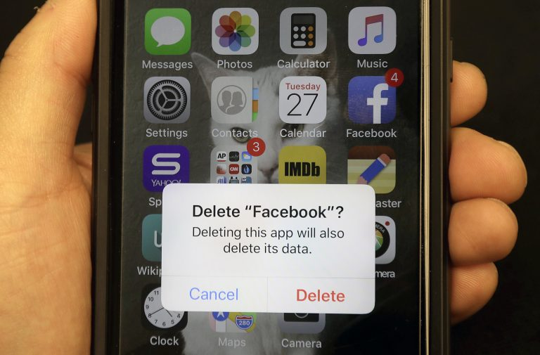 In this March 27, 2018, file photo, a reporter holds a phone showing the Facebook app in San Francisco. It might not seem like a big deal to have  long-forgotten accounts on social media linger. But with hacking in the news constantly, including a breach affecting 50 million Facebook accounts, you might not want all that data sitting around. (Jeff Chiu/AP Photo, File)