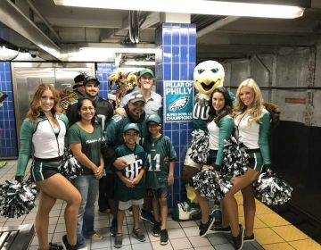 In this October 2018 photo provided by Matt Liston, Philadelphia Eagles fan Jigar Desai poses with his family, friends and members of the Philadelphia Eagles Cheerleaders in front of the subway pillar he ran into earlier this year at Ellsworth Station on the Broad Street subway line in Philadelphia. The moment in the spotlight isn't over yet for Desai who stumbled into fame as a viral video star after running into the subway pillar. Desai is now the subject of an NFL digital short feature, shot ahead of the Oct. 28 Eagles game against the Jacksonville Jaguars in London.  (Matt Liston via AP)