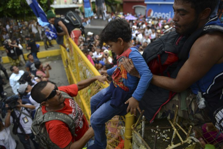 A child is carried over the border fence as thousands of Honduran migrants rush across the border towards Mexico, in Tecun Uman, Guatemala, Friday, Oct. 19, 2018. Migrants broke down the gates at the border crossing and began streaming toward a bridge into Mexico. After arriving at the tall, yellow metal fence some clambered atop it and on U.S.-donated military jeeps. Young men began violently tugging on the barrier and finally succeeded in tearing it down. (AP Photo/Oliver de Ros)