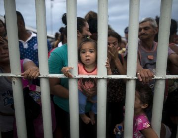 Migrants bound for the U.S.-Mexico border wait on a bridge that stretches over the Suchiate River, connecting Guatemala and Mexico, in Tecun Uman, Guatemala, Friday, Oct. 19, 2018.  The gated entry into Mexico via the bridge has been closed.  The U.S. president has made it clear to Mexico that he is monitoring its response. On Thursday he threatened to close the U.S. border if Mexico didn't stop the caravan. (AP Photo/Oliver de Ros)