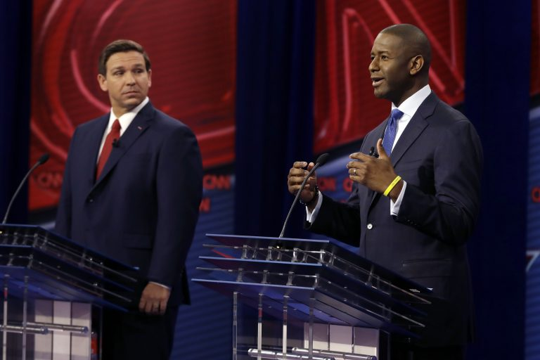 Florida Democratic gubernatorial candidate Andrew Gillum, right, speaks as Republican gubernatorial candidate Ron DeSantis looks on during a CNN debate, Sunday, Oct. 21, 2018, in Tampa, Fla. (AP Photo/Chris O'Meara)