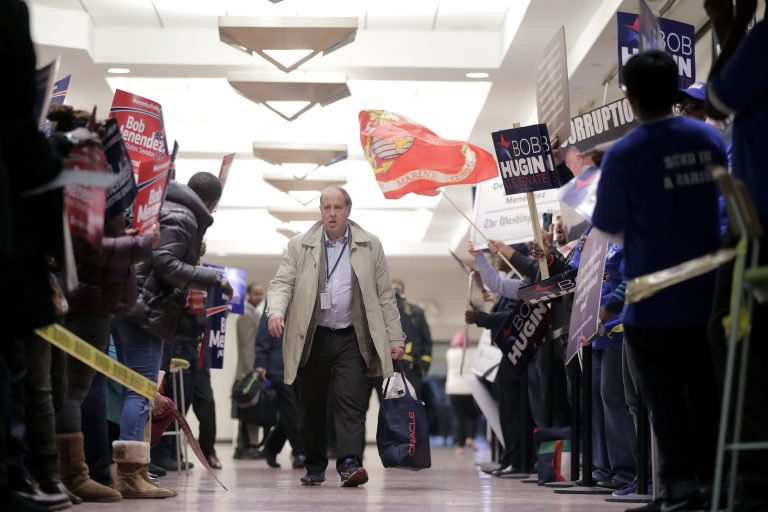 A pedestrian walks through a hallway as supporters of Democratic U.S. Senate candidate Bob Menendez, left, rallied against supporters of Republican candidate Bob Hugin outside of the NJTV Studios where the two are scheduled to engage in a debate, Wednesday, Oct. 24, 2018, in Newark, N.J. (AP Photo/Julio Cortez)