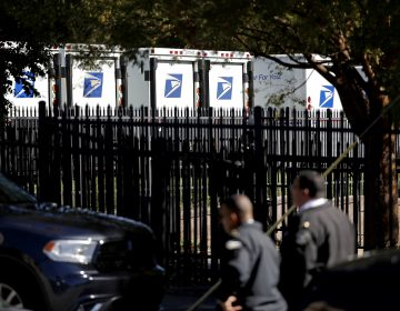 Law enforcement officials gather outside a U.S. post office facility after reports that a suspicious package was found in Atlanta, Monday, Oct. 29, 2018. (AP Photo/David Goldman)