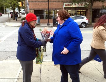 Kristin Wessell, right, hands a bouquet of flowers to Marianne Novy on Murray Avenue in the Squirrel Hill neighborhood of Pittsburgh, Monday, Oct. 29, 2018. Wessell was volunteering to bring some cheer to the neighborhood following Saturday's deadly attack on the nearby Tree of Life synagogue. Neither woman thinks President Trump should come to town. (AP Photo/Allen G. Breed)
