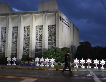 In this Oct. 28, 2018, file photo a Pittsburgh Police officer walks past the Tree of Life Synagogue and a memorial of flowers and stars in Pittsburgh in remembrance of those killed and injured when a shooter opened fire during services Saturday at the synagogue. (Gene J. Puskar/AP Photo, File)
