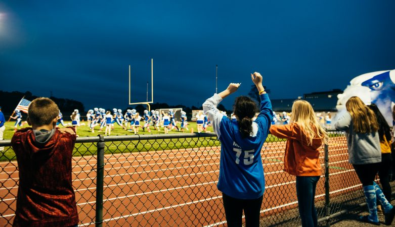 A student cheers as the football team runs on to the field for the start of the Kennard-Dale football game. (Dani Fresh for WHYY)