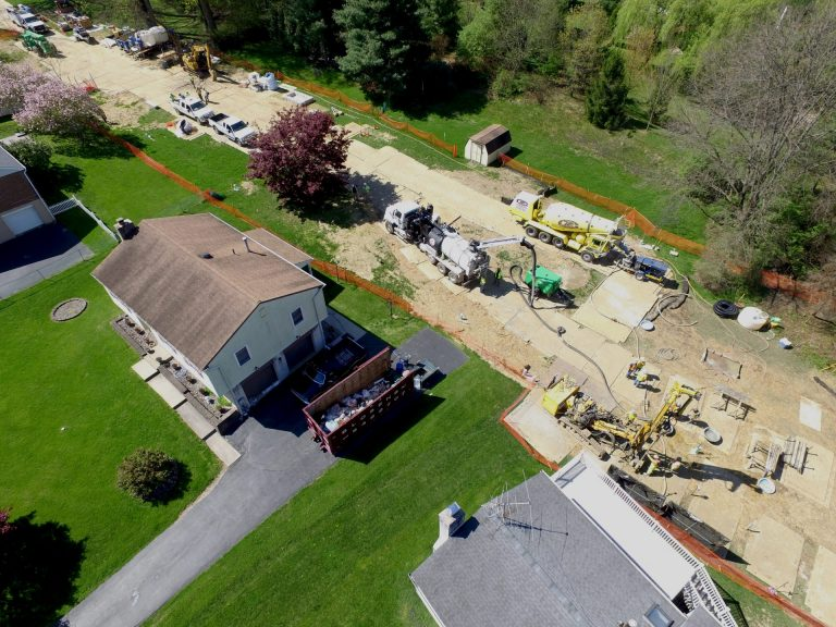 Mariner East 2 pipeline construction crews work in the backyards of homes on Lisa Drive in West Whiteland Township, Chester County, on May 2. Sinkholes that opened in the area prompted the state's Public Utility Commission to order that an existing pipeline nearby, the Mariner East 1, be shut down until it could be determined that the sinkholes didn't threaten its safety. PUC on May 3 approved a re-start of Mariner East 1. (Marie Cusick/StateImpact Pennsylvania)