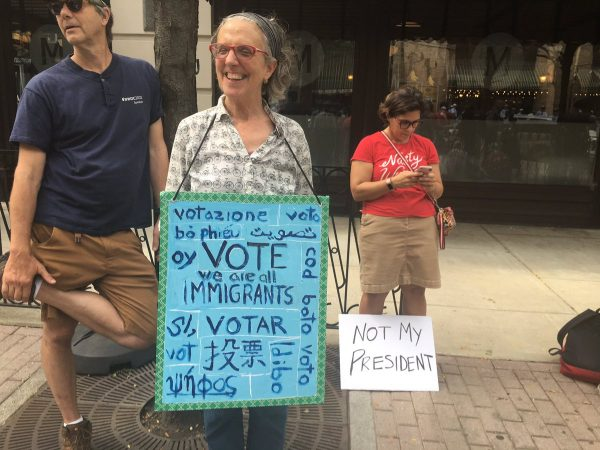 "Sarah Mceneaney says she's disappointed with the current federal immigration policies. ""I made a sign to encourage people to vote because that is what is going to make change ."" (Taylor Allen/WHYY)"