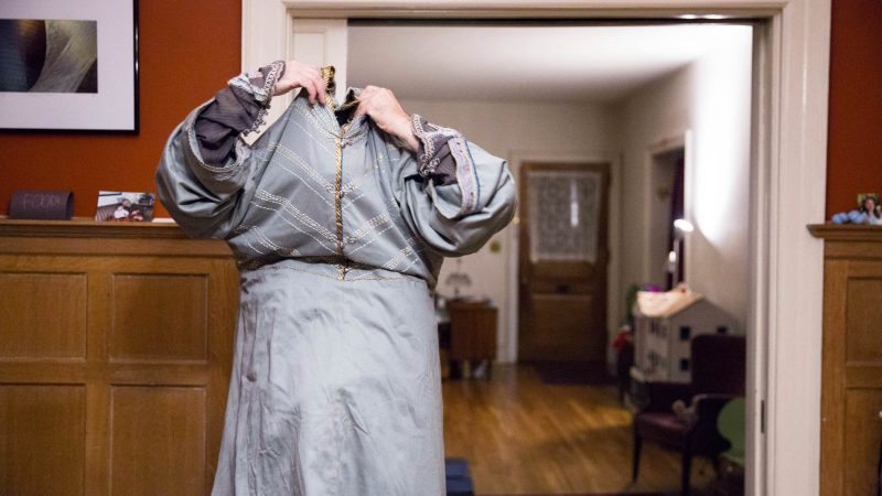 Walt Maguire pulls his floor-length Dumbledore robe over his head at his home in Germantown on the morning of Oct. 20, 2017. Maguire played the part of Dumbledore at the Chestnut Hill Harry Potter Festival for six years and would begin getting ready at 5 a.m. (Rachel Wisniewski for WHYY)