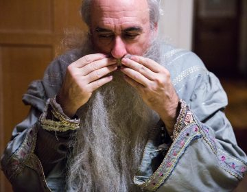 "Walt Maguire attaches Dumbledore's beard to his face using a temporary glue. Maguire feels great sadness about stepping down from his role as Hogwarts headmaster, saying that ""when I heard it was being discontinued, my first thought was a slight resentment that I didn't get to decide to stop."" (Rachel Wisniewski for WHYY)"