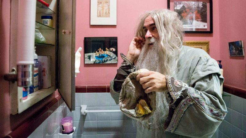 Walt Maguire adjusts his wig in his bathroom mirror. Maguire played the part of Dumbledore at the Chestnut Hill Harry Potter Festival for six years. (Rachel Wisniewski for WHYY)