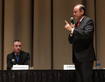 U.S. Rep. Brian Fitzpatrick, a Republican, listens to his Democratic challenger in Pennsylvania's 1st Congressional District, Scott Wallace, during a debate at Delaware Valley University in Doylestown. (Emma Lee/WHYY)