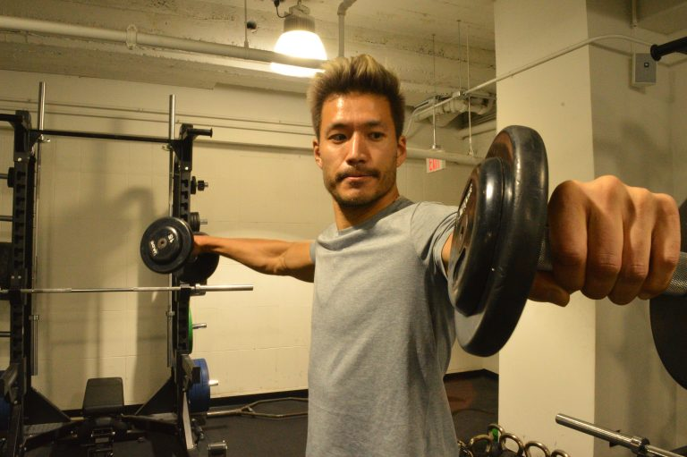 Kevin Kreider, a model and former bodybuilder, lifts weights at his local gym. Kreider says he quit pre-workout after becoming addicted. (Liz Tung/WHYY)