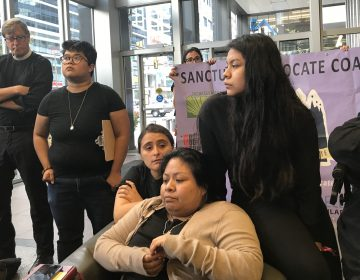 Carmela Apolonio Hernandez (center), and her daughter Keyri (right), wait in the lobby of 2000 Market Street for a visit with Senator Bob Casey's staff Wednesday morning. (Laura Benshoff/WHYY)