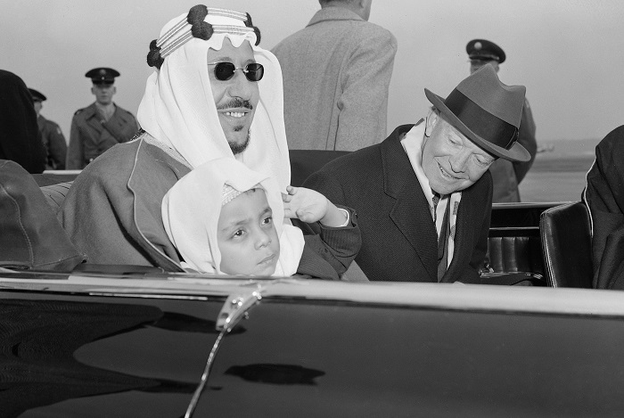 Six-year-old Prince Mashhur ibn Saud waves as he sits on the lap of his father, King Saud of Saudi Arabia, and beside President Eisenhower as they left National Airport, January 30, 1957.  The King and his official party will visit here three days for talks with the President.  (AP Photo)