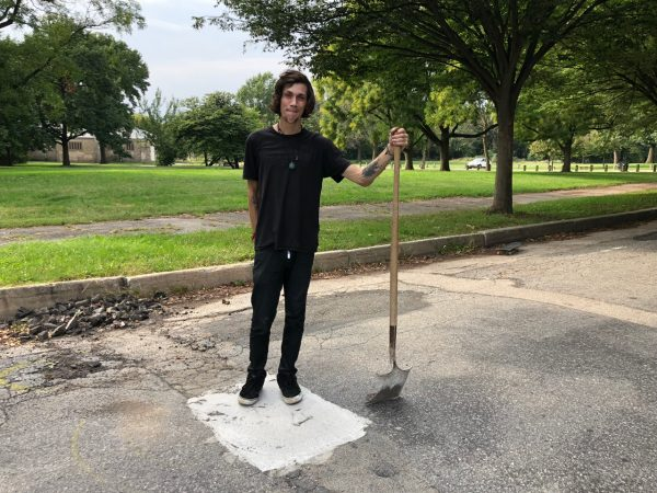 Skater Dickey Johnston stands on a pothole at FDR Park he helped repair. (Meir Rinde for WHYY)
