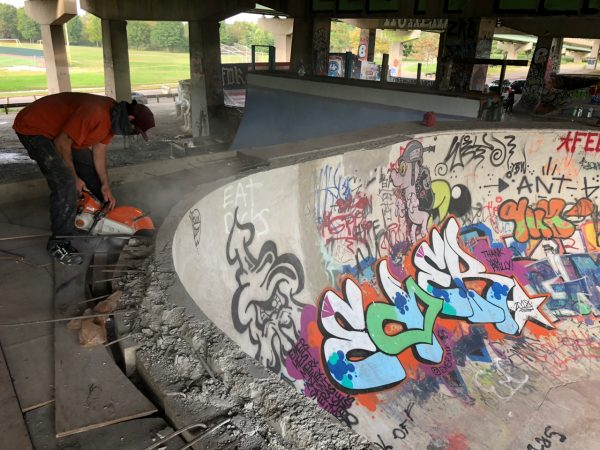 A skater cuts concrete around a bowl at the skatepark in FDR Park. (Meir Rinde for WHYY)