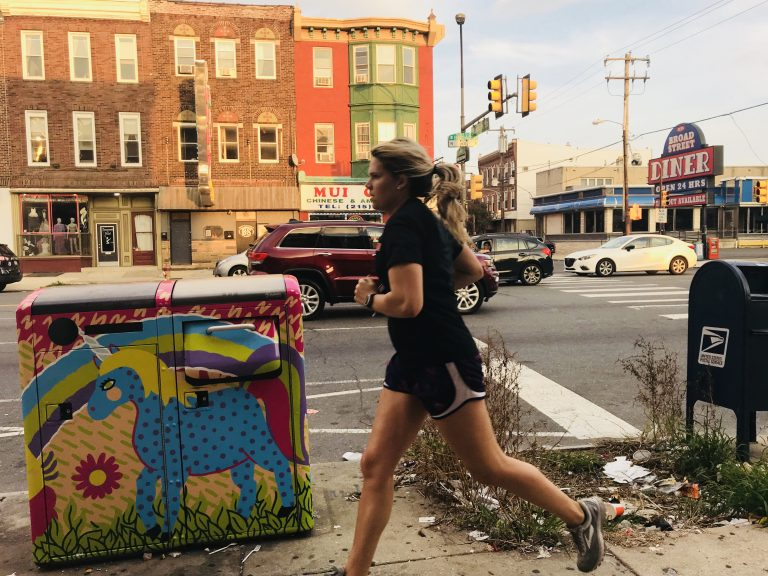 A woman runs past a pile of litter next to a Big Belly trash can on South Broad Street. (Ariella Cohen/WHYY)