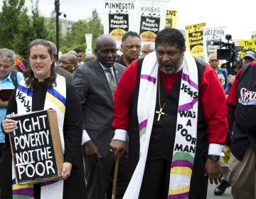 The Rev. William Barber marches outside the U.S. Capitol during a Poor People's Campaign rally in June. On the left is co-leader of the Poor People's Campaign, the Rev. Liz Theoharis. (Jose Luis Magana/AP)